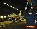 US Navy 110320-F-NI989-135 A crew chief from the 52nd Aircraft Maintenance Squadron marshals an F-16 Fighting Falcon out of a hardened aircraft she.jpg