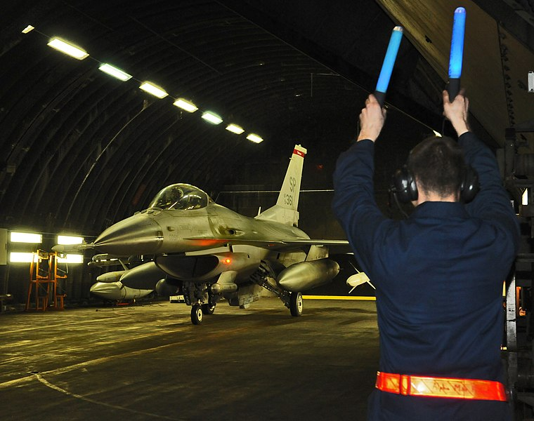 File:US Navy 110320-F-NI989-135 A crew chief from the 52nd Aircraft Maintenance Squadron marshals an F-16 Fighting Falcon out of a hardened aircraft she.jpg