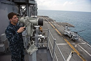 US Navy 111214-N-DX615-129 Seaman Patrick Barth looks for contacts while standing the forward lookout watch aboard the amphibious assault ship USS.jpg