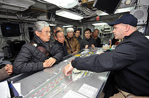 US Navy 120202-N-KM939-008 Lt. Cmdr. Dave Hecht conducts a tour of Flight Deck Control with Japanese visitors aboard the nuclear-powered aircraft c.jpg