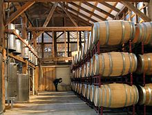 A wood-paneled warehouse with stainless steel fermentation tanks on the left, and rows of oak barrels on the right.