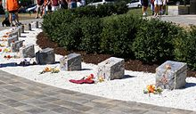 Blocks of stone arranged in a semi-circle in a bed of white gravel with a paved walkway in front and green bushes behind.