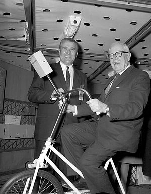 George Paul Miller - During a 1968 visit to the Marshall Space Flight Center, the House Committee on Science and Astronautics toured the S-IVB workshop. Pictured here are Wernher von Braun (standing) and Congressman Miller (sitting on the ergometer bicycle) inside the workshop.