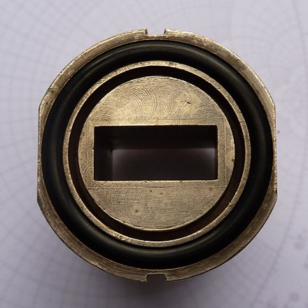Figure 5. RCSC 5985-99-083-0003 choke flange through-mounted on WG16 (WR90) waveguide. Machining down the end of the waveguide tube has left a clear pattern across the recessed face and the end of the tube. The flats on either side of the flange are to allow a threaded collar to be manoeuvred over it, while the notches at the top and bottom are for alignment. The O-ring for pressurization is in place. Waveguide-choke-flange-through-mounted.jpg