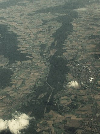 Wesergebirge - The Weser Hills seen from the west. In the left foreground Bad Eilsen and behind that the Bückeberge; in the right foreground Rinteln with a few meanders of the Weser river (right margin). The background shows a few more forested elevations of the Weser Uplands.