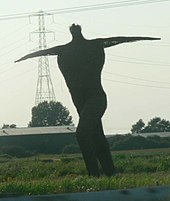 Large statue of a human figure with arms outstretched. In the background are trees and an electricity pylon.
