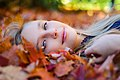 Woman lying in autumn leaves (Unsplash).jpg