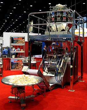 Vertical form fill sealing machine - XtraVac Multihead weigher inclined vffs vertical form fill seal packaging machine with a simple conveyor and rotary catching table - Taken at Pack Expo Chicago 2014