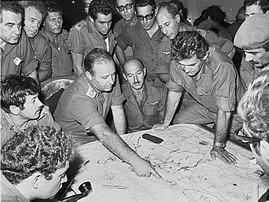 Réunion du Commandement régional du Nord de l'Armée de défense d'Israël lors de la guerre du Kippour, le 10 octobre 1973. L'homme qui pointe l'index est Yitzhak Hofi, celui aux deux mains sur la carte est David Elazar, chef d'État-Major, l'homme aux lunettes foncées se tenant debout derrière eux est Rehavam Zeevi. (définition réelle 1800×1350)
