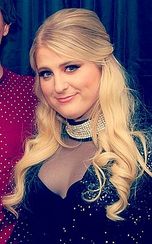 Meghan Trainor is looking into the camera.