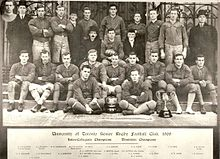 Twenty-five men, divided into three rows, pose.  The majority are wearing football uniforms, except for four executives in suits.  Two trophies are placed in front of the players.