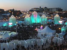 hundreds of spectators in front of the ice castle which is lit blue-green from inside