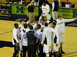 Men's basketball team in a pre-game huddle on the court