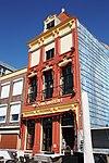 foto van Huis met in 19e eeuw vernieuwde lijstgevel en oude kern. Hoge kap bekroond met houten piron. Dakkapel