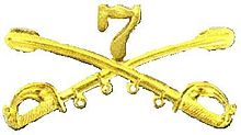 A computer generated reproduction of the insignia of the Union Army 7th Regiment of Cavalry. The insignia is displayed in gold and consists of two sheafed swords crossing over each other at a 45 degree angle pointing upwards with a Roman numeral 7