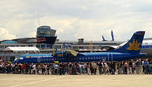 Blue aircraft on static display, surrounded by onlookers. Buildings make up the background.