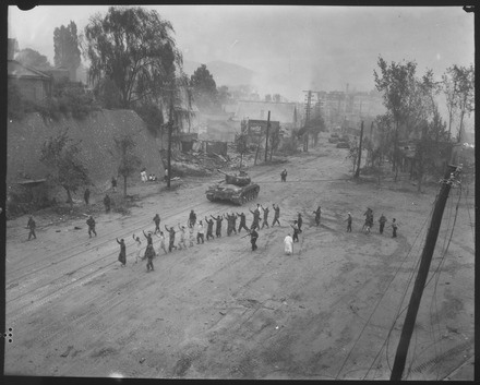 Pershing tanks in downtown Seoul during the Second Battle of Seoul in September 1950. In the foreground, United Nations troops round up North Korean prisoners-of-war. A U.S. Marine tank follows a line of prisoners of war down a village street. - NARA - 532408.tif