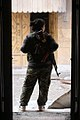 A YPJ fighter with a rifle on her back checks the street.jpg
