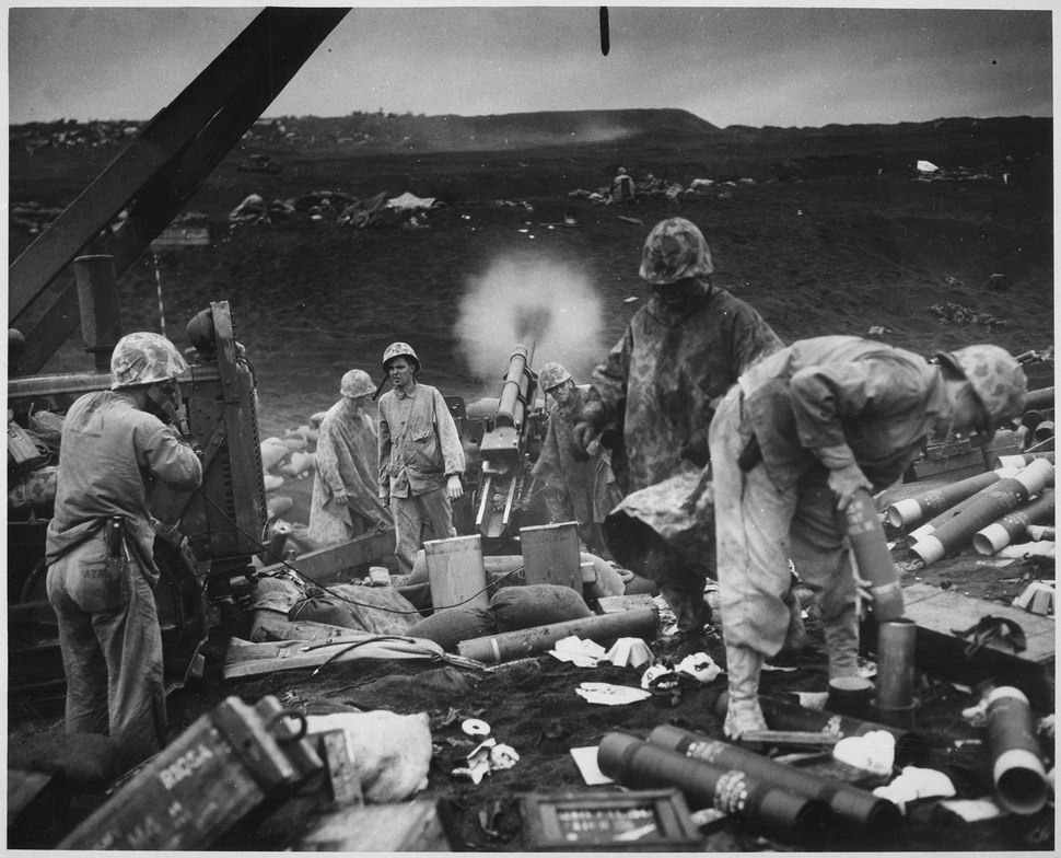 Across the litter on Iwo Jima's black sands, Marines of the 4th Division shell Japanese positions cleverly concealed... - NARA - 513219