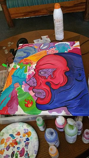 An acrylic painting of a red and blue face in profile lies on top of a tray on a table. Below the painting, on the table, are a palette and various sizes and colors of paint.