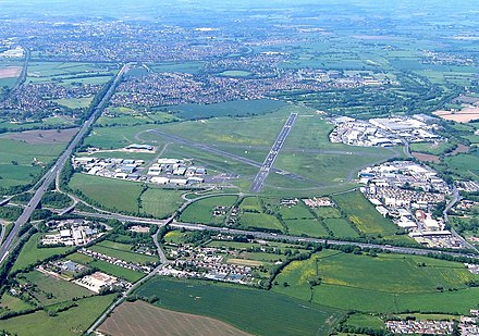 Gloucestershire Airport in 2017, looking east. On the left is the straight A40 road and at the bottom the M5 motorway. Innsworth and Gloucester are at the top. Aerial of Gloucestershire Airport, Gloucestershire, England 24May2017 arp.jpg