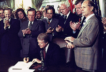 Carter surrounded by a crowd of people as he signs the Airline Deregulation Act.