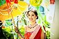 An Indian girl holding an umbrella for a Hindu wedding ceremony.jpg
