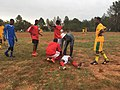 An injured player lying down during a soccer game. Cosmo City, South Africa.jpg