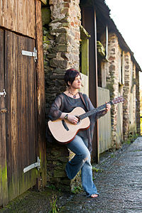 Ange Hardy standing with Martin 000-16 guitar.jpg