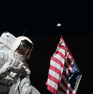 Lunar Flag Assembly - Harrison Schmitt poses by the American flag deployed on Apollo 17, December 11, 1972. The Earth is visible above the flag, which used to hang on the wall in the Mission Operations Control Room.