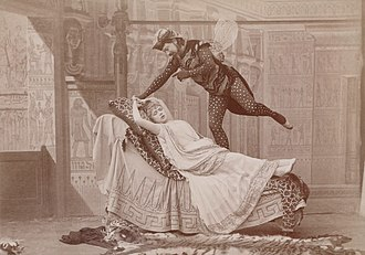 Мужчина в костюме гигантской мухи парит над лежащей молодой женщиной