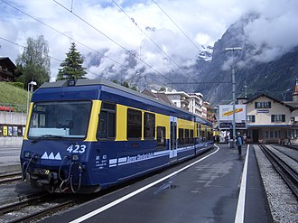 Bernese Oberland Railway - A modern low-floor train of the BOB in Grindelwald with the track of the Wengernalpbahn on the adjacent platform. Note the modern blue / yellow BOB livery.