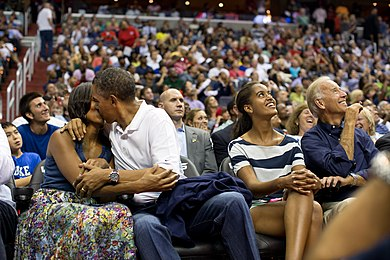 US President Barack Obama and his wife Michelle Obama kissing for the kiss cam while Malia Obama and Joe Biden watch on the jumbotron during a basketball game in Washington, DC Barack and Michelle Obama kissing at a basketball game.jpg