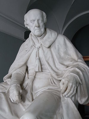 "John Rolle, 1st Baron Rolle - Sculpture of Lord Rolle (died 1842), inscribed on plinth: ""E.B. Stephens sculp. London 1844"", in entrance hall of Bicton House, Exeter, Devon. By Edward Bowring Stephens (1815–1882); exhibited at the Royal Academy, London, as: ""A marble statue of the late Lord Rolle in the robe worn at the coronation of Her Majesty the Queen"". An identical earlier version dated 1843 exists in the entrance hall of Lupton House, Brixham, the home of John Yarde-Buller, 1st Baron Churston (1799–1871)"