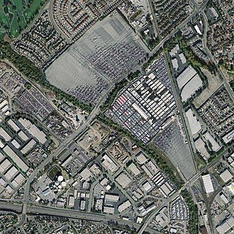 San Jose Flea Market - Aerial photograph of Berryessa Flea Market (2003). Berryessa Road runs diagonally, from upper right to lower left, dividing the site into north and south parcels. Bayshore Freeway runs horizontally in the lower part of the photograph.