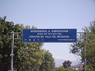 "A large overhead road sign says ""BIENVENIDOS A IXMIQUILPAN"", then (smaller) ""HOGÄ EHE NTS'U̲TK'ANI"", then (larger again) ""CORAZON DEL VALLE DEL MEZQUITAL""."