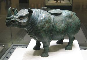 Northern Sumatran rhinoceros - A wine vessel in the form of a bronze two-horned rhinoceros with silver inlay, from the Western Han (202 BC – 9 AD) period of China, sporting a saddle on its back.