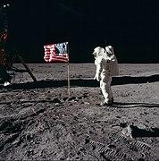 Photographie en couleur de Buzz Aldrin près du drapeau américain planté sur la Lune.