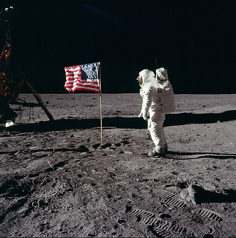 Buzz Aldrin salutes the U.S flag on the Moon (mission time: 110:10:33). His fingertips are visible on the far side of his faceplate. Note the well-defined footprints in the foreground. Buzz is facing up-Sun. There is a reflection of the Sun in his visor. At the bottom of Buzz's faceplate, note the white 'rim' which is slightly separated from his neckring. This 'rim' is the bottom of his gold visor, which he has pulled down. We can see the LEC straps hanging down inside of the ladder strut. In the foreground, we can see the foot-grabbing loops in the TV cable. The double crater under Neil's LM window is just beyond the LM shadow.