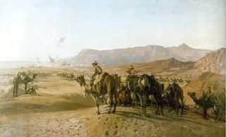 A large number of men mounted on camels in a treeless desert. There is a town in the distance, and bare rocky mountains beyond.