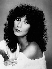 Cher with black curly hair, wearing a white dress