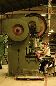 Seated female workers making knives on machinery with large spinning drums