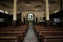 Interior de la iglesia con bancos de madera, techo decorado y grandes columnas