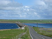 The causeway, made from many concrete blocks, carries a road between the islands. The sea is rough on one side of the barrier but calm on the other.