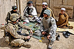 Defense.gov News Photo 120317-A-8536E-245 - U.S. Army 2nd Lt. Jeffery Russell left sits with his interpreter Zorro an Afghan soldier and residents during an event with leaders in the.jpg