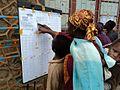 Des électeurs parcourent les listes électorales dans un centre de vote (Collège Alfajiri) à Bukavu (6424786449).jpg