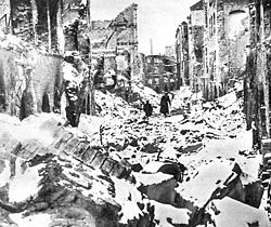 Black and white photo of ruins of buildings in Warsaw. In the distance, two black figures can be seen walking through the rubble.