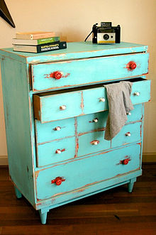A dresser with a distressed finish and mismatched drawer knobs, in Shabby  chic style