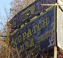 A billboard with peeling paint and faded yellow lettering that reads Dogpatch, USA: free admission.