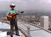 1980 colour photograph of Donn Reynolds performing outside atop the main deck roof of the CN Tower (Toronto, Ontario, Canada).